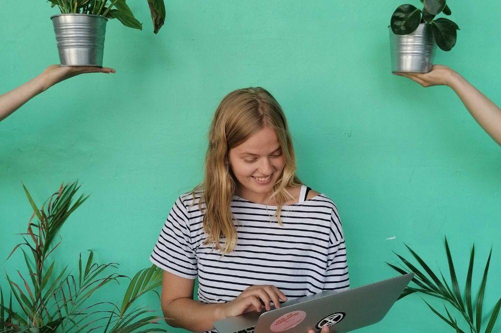 Eine Person arbeitet an einem Laptop. Um sie herum sind Pflanzen.