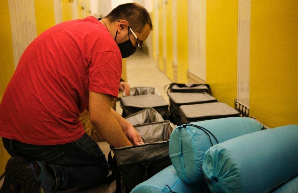 Joshua packt Schlafsäcke für Menschen ohne Obdach