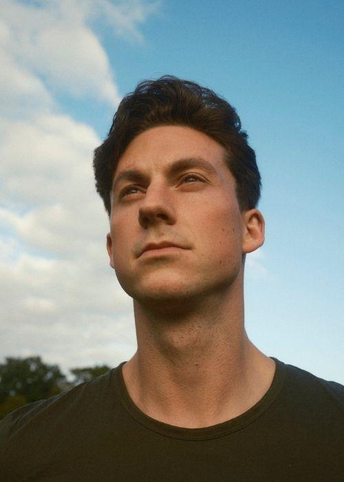 Auf dem Bild ist ein Mann zu sehen. Im Hintergrund ist blauer Himmel mit Wolken zu sehen. Der Mann trägt ein dunkles Oberteil und schaut in die Luft.