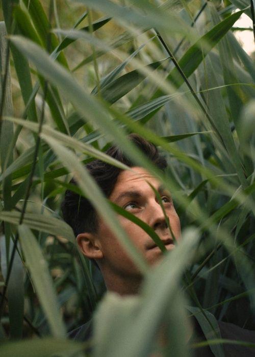 Ein Mann steht inmitten von grünem Gestrüpp.