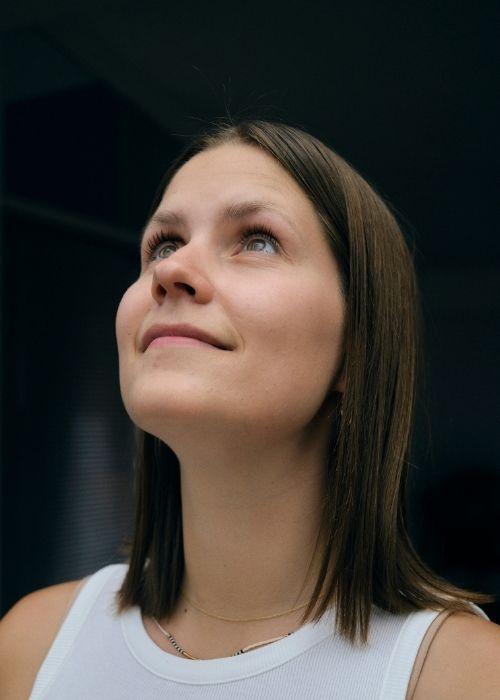 Die Frau auf dem Bild schaut nach oben Links. Sie trägt ein weißes Top und steht vor einem dunkeln Hintergrund.
