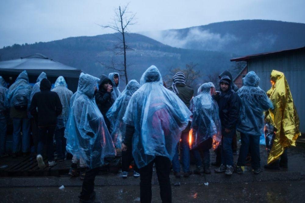 Auf dem Bild sind Menschen zu sehen, die weiße Regenponchos tragen. Im Hintergrud sind Zelte. Dieses Bild zeigt Personen, die geflüchtete Menschen versorgen